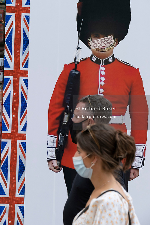 Masked shoppers walk beneath the image of a guardsman whose face has been obscured by an anti-vaxx message mocking pandemic face coverings, on Covid 'Freedom Day'. This date is what Prime Minister Boris Johnson's UK government has set as the end of strict Covid pandemic social distancing conditions with the end of mandatory face coverings in shops and public transport, on 19th July 2021, in London, England.
