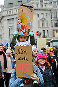 A young child with a homemade banner at the Bread and Roses Womens March on January 19, 2019 in London, England.  The event was dubbed the Bread and Roses March based on the strikes of the same name by textile workers in Massachusetts in 1912 and Bread and Roses is the title of a poem by American poet James Oppenheim about the strikes.
