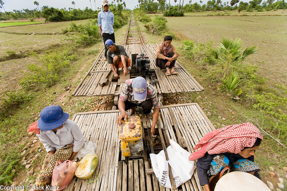 """01 JULY 2006 - PHNOM PENH, CAMBODIA: The bamboo train in back pushes the bamboo train in front after the first one ran out of gas on the tracks in central Cambodia. The """"bamboo trains"""" run along the government tracks in rural Cambodia. Bamboo mats are fitted over wheels which ride on the rails. The contraption is powered by a either a motorcycle or lawn mower engine. The Cambodian government would like to get rid of the bamboo trains, but with only passenger train in the country, that runs only one day a week, the bamboo trains meet a need the government trains do not. While much of Cambodia's infrastructure has been rebuilt since the wars which tore the country apart in the late 1980s, the train system is still in disrepair. There is now only one passenger train in the country. It runs from Phnom Penh to the provincial capitol Battambang and it runs only one day a week. It takes 12 hours to complete the 190 mile journey.  Photo by Jack Kurtz / ZUMA Press"""