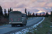 Park bus driving on the main road in Denali National Park at sunset, Alaska