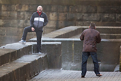 """© Licensed to London News Pictures. 09/11/2015. Bridlington, UK. FRAME 9 OF 9. A man poses for a photograph on the sea defences at the sea side town of Bridlington & gets caught out by a huge wave. The Yorkshire region was hit by severe gales this afternoon with winds up to 60mph. The Met Office warned West Yorkshire to expect gales and locally severe gales over high ground, with some """"very gusty"""" winds to the east of high ground as well.<br /> Photo credit: Andrew McCaren/LNP"""