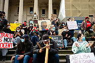 A man is seen playing a didgeridoo with protesters holding placards behind him during a Black Lives Mater rally on 06 June, 2020 in Melbourne, Australia. This event was organised to rally against aboriginal deaths in custody in Australia as well as in unity with protests across the United States following the killing of an unarmed black man George Floyd at the hands of a police officer in Minneapolis, Minnesota. (Photo by Dave Hewison/ Speed Media)