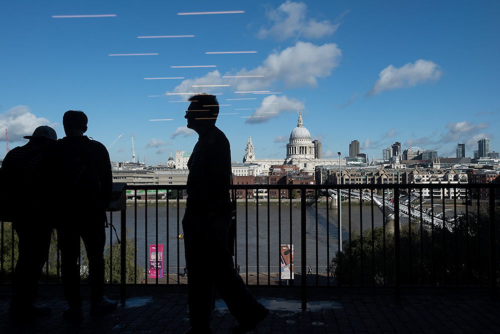 London, UK - 8 October 2014: Neons reflected in the window of Tate Modern Gallery as people look at the view on the City and St. Paul's Cathedral