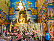 "30 JANUARY 2016 - NONTHABURI, NONTHABURI, THAILAND: Inside the ""viharn,"" or main prayer hall, at Wat Bua Khwan, a large Buddhist temple in Nonthaburi, north of Bangkok, Thailand. The money hanging in the center is donations from people who come to the temple.         PHOTO BY JACK KURTZ"