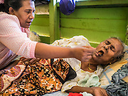 02 JUNE 2015 - KULAI, JOHORE, MALAYSIA: ZAHIDA, a Rohingya refugee in Kulai, Malaysia, feeds her mother, ASMA, 90 years old, in their home in Kulai. They came to Malaysia on a boat with 50 members of their extended family. They paid traffickers 250,000 Malaysian Ringgits (about $65,000 US) to bring them to Malaysia via traffickers' camps in Thailand. The UN says the Rohingya, a Muslim minority in western Myanmar, are the most persecuted ethnic minority in the world. The government of Myanmar insists the Rohingya are illegal immigrants from Bangladesh and has refused to grant them citizenship. Most of the Rohingya in Myanmar have been confined to Internal Displaced Persons camp in Rakhine state, bordering Bangladesh. Thousands of Rohingya have fled Myanmar and settled in Malaysia. Most fled on small fishing trawlers. There are about 1,500 Rohingya in the town of Kulai, in the Malaysian state of Johore. Only about 500 of them have been granted official refugee status by the UN High Commissioner for Refugees. The rest live under the radar, relying on gifts from their community and taking menial jobs to make ends meet. They face harassment from Malaysian police who, the Rohingya say, extort bribes from them.     PHOTO BY JACK KURTZ