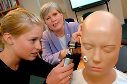 Medical student learns how to examine the ear with a GP at a new training clinic; Bradford Yorkshire UK