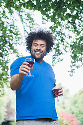 Happy young man outdoors with glass of wine