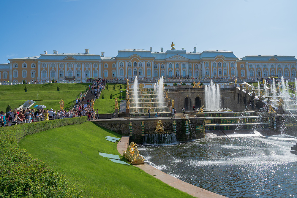 Peterhof, Russia -- July 21, 2019. Wide angle photo of tourists and the fountains  in the  garden behind the Summer Palace in Peterhof.