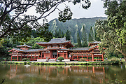 """The peaceful Byodo-In Temple reflects in a pond in Valley of the Temples Memorial Park, at 47-200 Kahekili Highway, Kaneohe, on the island of Oahu, Hawaii, USA. The Byodo-In Temple (""""Temple of Equality"""") was built in 1968 to commemorate the 100 year anniversary of the first Japanese immigrants to Hawaii. This Hawaii State Landmark is a non-practicing Buddhist temple which welcomes people of all faiths. The beautiful grounds at the foot of the Ko'olau Mountains include a large reflecting pond stocked with Japanese koi carp, meditation niches, and small waterfalls. Byodo-In Temple in O'ahu is a half-scale replica of the Byodo-in Temple built in 1053 in Uji, Japan (a UNESCO World Heritage Site)."""
