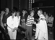 """Fr Niall O'Brien says Thanksgiving Mass.1984..16.07.1984..07.16.1984..16th July 1984..In celebration of his safe homecoming from the Philippines,Fr Niall O'Brien said a thanksgiving mass At Newtownpark Ave,Blackrock,Dublin. Along with two other priests and six lay people,Fr Niall was falsly accused of multiple murders.They became known as """"The Negros Nine"""".After President Reagan visited Ireland,The American government put pressure on the Marcos regime and all charges were dropped and all were fully exonerated...Image taken as Fr O'Brien shakes the hands of some of the congregation in the """"Peace Be with you"""" part of the Mass...Note; Fr O'Brien, who was born in Dublin in 1939,died in Pisa, Italy in 2004"""