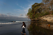 A lady wearing a hijab walks towards the sea at Batu Karas beach on the 31st October 2019 in Java in Indonesia.