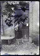 severely eroding glass plate of woman standing and holding a parrot