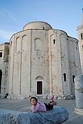 Child (5 years old) resting on ancient Roman column, in front of Saint Donatus' Church (Crkva sveti Donata). Zadar, Croatia