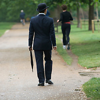 Man in smart city suit and bowler hat walking  in Hyde Park, London