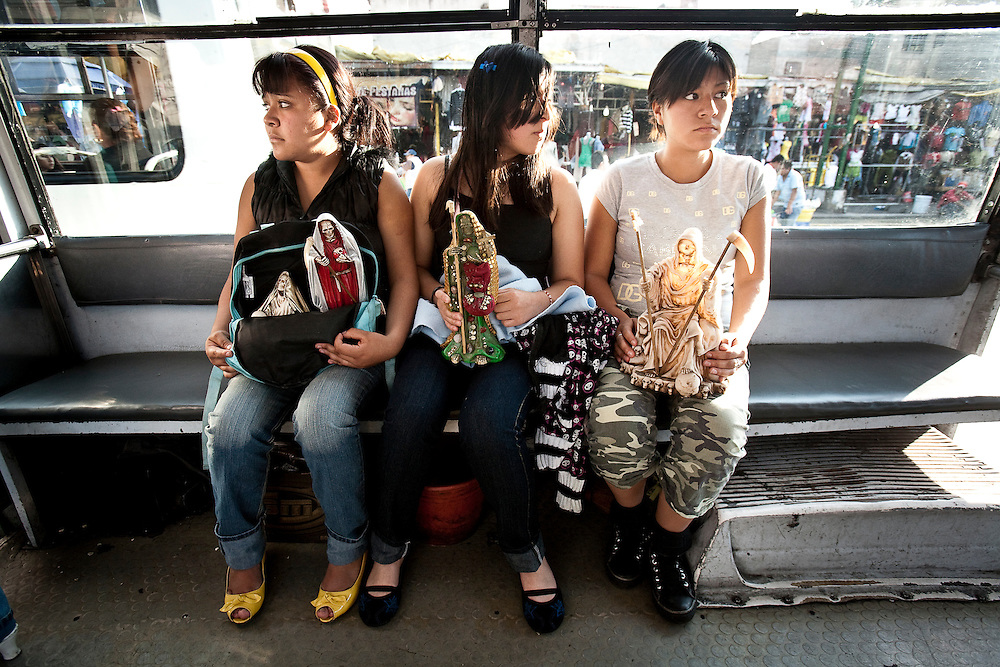 Three teenagers travel across Mexico city to the Tipito Sante Muerte Shrine with thier Sante Muerte figures in Mexico City.