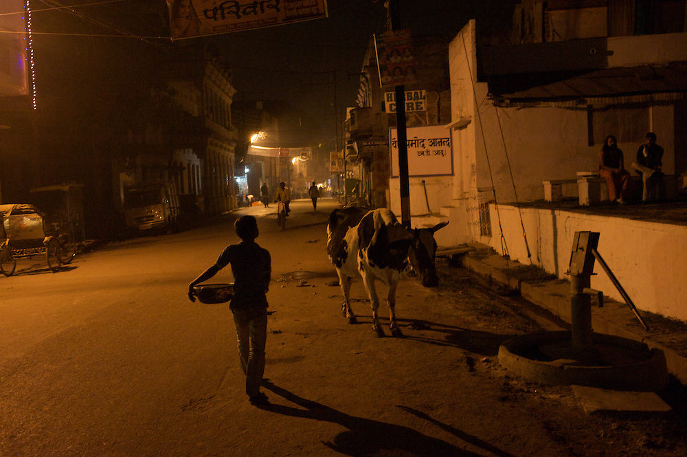 A young boy walks home at the end of a long day of selling candles along the Ganges River in Varanasi, India