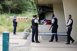 © Licensed to London News Pictures. 23/07/2020. London, UK. Police officers guard the crime scene on Broadwater Farm Estate, Tottenham in north London. A man is fighting for his life in hospital after a triple shooting in Tottenham, during the early hours of this morning. Police were called to shots fired on Griffin Road, where three men were found suffering from gunshot wounds. Photo credit: Dinendra Haria/LNP