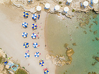 Aerial view of blue and white parasols on the shore of Rhodes island, Greece.