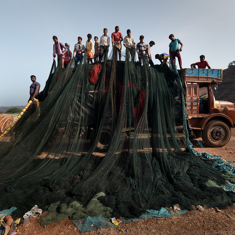 From the top of a truck, many fishermen fold a gigantic fishing net.