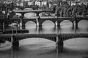 Monochrome photo of five of the 18 bridges across the Vltava River in Prague, Czech Republic