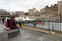 © Licensed to London News Pictures. 22/12/2015. London, UK. A tourist eats an ice cream near the Tower of London ice rink. The Tower of London ice rink has been forced to close today due to safety concerns over high wind speeds.  The UK is experiencing unseasonably mild weather and high winds today. Photo credit : Vickie Flores/LNP