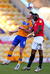 Ollie Clarke of Mansfield Town and Yann Songo'o of Morecambe jump to head the ball - Mandatory by-line: Ryan Crockett/JMP - 27/02/2021 - FOOTBALL - One Call Stadium - Mansfield, England - Mansfield Town v Morecambe - Sky Bet League Two