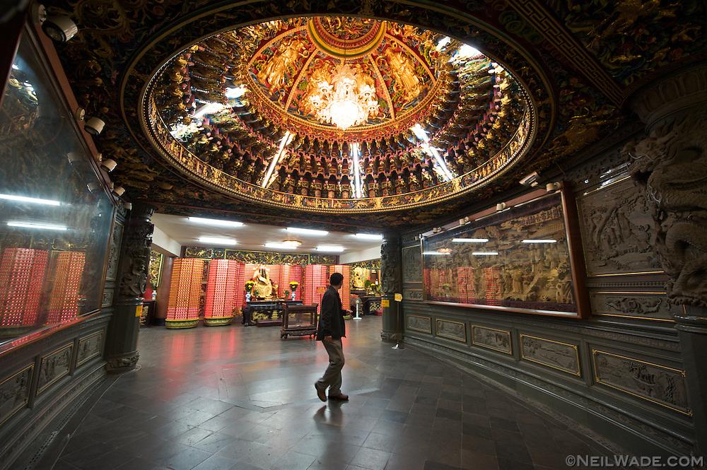 A man walks through a hallway into Guandu Daoist Temple in Taipei, Taiwan.
