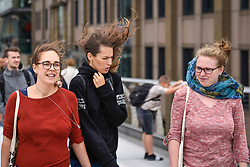 © Licensed to London News Pictures. 10/08/2019. LONDON, UK.  Women cross the Millennium Bridge during windy conditions.  Much of the UK forecast to be subject to strong winds for the weekend.  Photo credit: Stephen Chung/LNP