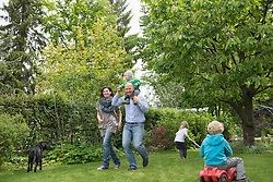 Parents playing in garden with three small kids