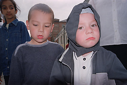 Two primary school boys standing in playground looking serious,