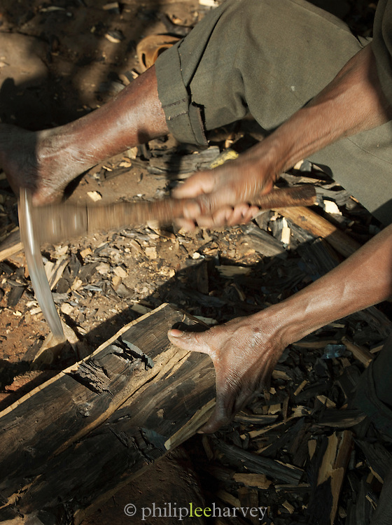 An artisan carves a piece of wood, making it into a statue for sale in a market in Bamako, Mali