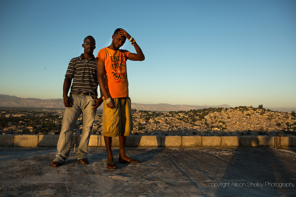 """Horlich Florestal, 29, L, and Rosemond Altidon, 27, R, stand on the roof of their apartment building, half of which was destroyed in the earthquake of January 12, 2010, in the Fort National neighborhood of Port-au-Prince, January 4, 2015.  They both still live in the building, and Alton helped convert the building's ragged edges into a balcony. Said Florestal, """"I was completely scared when that quake happened because I had never felt an earthquake before.  Many of my neighbors, including two cousins and their aunt, died when our building fell apart.  I didn't know if life would continue.  Everything was gone.  Life was gone."""""""