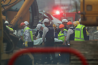 A body is removed from the rubble of the CTV building in Christchurch City Centre after a Powerful earth quack ripped through Christchurch, New Zealand on Tuesday lunch time killing at least 65 people as it brought down buildings, buckled roads and damaged churches and the Cities Cathedral. Photo Tim Clayton