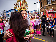 """29 APRIL 2017 - MINNEAPOLIS, MINNESOTA: A participant in the parade gets a congratulatory hug during the parade at Songkran Uptown. Several thousand people attended Songkran Uptown on Hennepin Ave in Minneapolis for the city's first celebration of Songkran, the traditional Thai New Year. Events included a Thai parade, a performance of the Ramakien (the Thai version of the Indian Ramayana), a """"Ladyboy"""" (drag queen) show, and Thai street food.     PHOTO BY JACK KURTZ"""