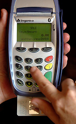 File photo dated 10/05/06 of someone using a chip and pin machine. Nearly 1.4 billion card payments were made in June, marking a monthly record high, according to a trade body.