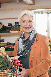 Portrait of a mature woman buying vegetables in the farm and smiling, Bavaria, Germany