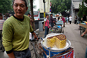 "Man selling a type of sweet nut cake outside Yonghe Temple, also known as the ""Palace of Peace and Harmony Lama Temple"", the ""Yonghe Lamasery"", or - popularly - the ""Lama Temple"" is a temple and monastery of the Geluk School of Tibetan Buddhism located in the northeastern part of Beijing, China. It is one of the largest and most important Tibetan Buddhist monasteries in the world. The building and the artworks of the temple is a combination of Han Chinese and Tibetan styles."