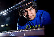 Composer Sebastian Sosa of Costa Mesa, CA, is reflected in the fallboard of a grand piano. Sosa started composing when he was in seventh grade.