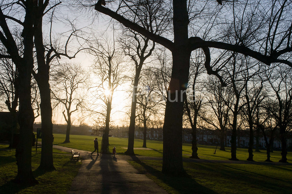 Mother and child enjoy spring weather in Ruskin Park in the south London borough of Lambeth. Looking into late sunlight, we see the two figures walking downhill beneath tall ash trees planted over 100 years ago. This is a large public space in SE24 used by locals from many miles because of its panoramic views across the capital.