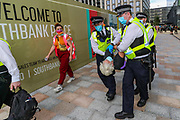 A police officer wearing face masks (L) carrying belongings of an arrestee who is being carried Police wearing face masks (R), meanwhile a legal observer (C) wearing an orange jacket is observing the process. The arrestee is suspected to have sprayed 'STOP ECOCIDE' outside Shell Headquarters building in Jubilee Gardens, Central London, on Tuesday, Sept 8, 2020. Protestors are seeking to step up pressure on Shell and demand an end on fossil fuel extraction as well as ecocide. Environmental nonviolent activists group Extinction Rebellion enters its 8th day of continuous ten days protests to disrupt political institutions throughout peaceful actions swarming central London into a standoff, demanding that central government obeys and delivers Climate Emergency bill. (VXP Photo/ Vudi Xhymshiti)