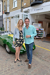 CLEMMIE ST.JOHN-WEBSTER and JAMIE DUNDAS at the launch of Dundas London held at Fiskins Classic Car Showroom, 14 Queens Gate Place Mews, London on 25th June 2014.