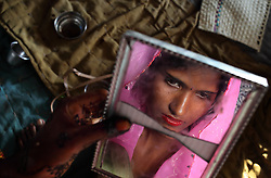 Radha Bhamwari, 15-years-old, looks at herself in a cracked mirror the day before her wedding in Rajasthan, India on April 26, 2009.