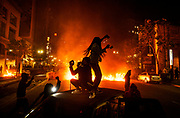 Two women dance on a car as a fire burns near 19th Street Bart station in Oakland, Friday, May 29, 2020. Demonstrators gathered Friday night in Oakland to protest the death of Minneapolis man George Floyd.