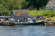 Lobster boat sitting idle at dock. Lots of lobster buoys, lobster traps, a flag flying in the yard, an old boathouse with an orange lichen growing on the roof, quintessential Maine.