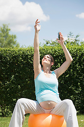Stretching pregnant woman garden fitness
