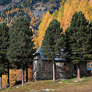 BOLZANO, ITALY - OCTOBER 14:    .A a house is hidden behind trees in a forest in Solda that as Autumnal colours appearing  on October 14, 2010 in Bolzano, Italy. Italy is currently enjoying the final warm spells of the summer, however, the shortening daylight hours and cooler weather is bringing Autumn foliage colours across the country.