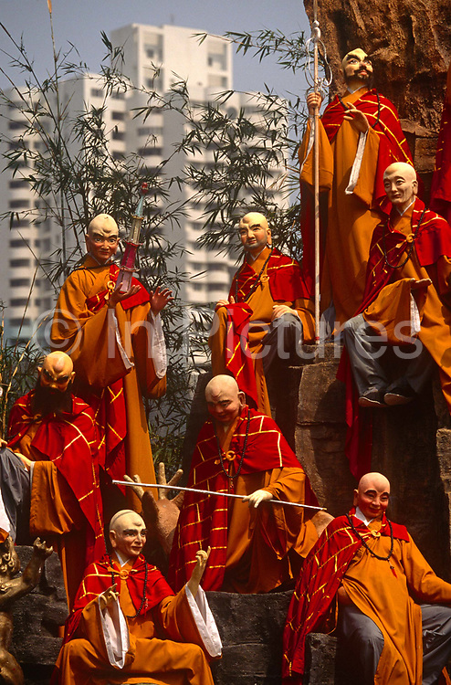 Historical monk figures in 'Splendid China' model village and modern architecture in the Shenzhen metropolis, China. This foreground is of China's history represented by a classical dynasty and the looming presence of the modern concrete city. We see some of the 50,000 ceramic figures and scenes from a period in Chinese history and further away, a modern corporate building in the metropolis contrasting with ancient, traditional architecture. Splendid China is an attraction at the Overseas Chinese Town, Shenzhen that has scaled down replicas of China's historical buildings, wonderful scenes and folk customs. The scale models are of a 1:15 with 100 miniaturized landmarks such as The Terracotta Warriors; Great Wall; Forbidden City; Old Summer Palace etc. all laid out according to their geographic locations.