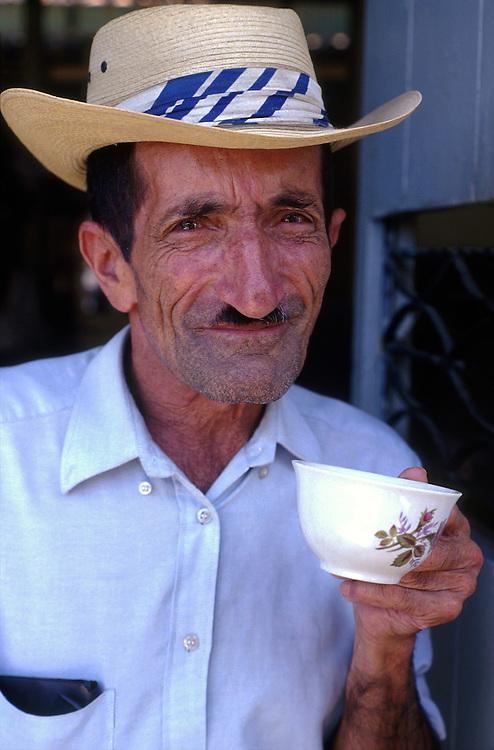 A local man in El Jardin, sips a cup of tinto - black coffee - not for export, Manizales, Coffee region (Zona Cafetero)