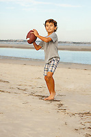 A young boy prepares to throw a football while playing on the beach.