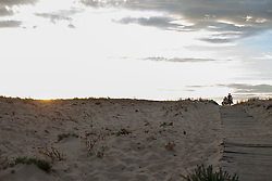 Tourists walking on boardwalk on the beach during sunset, Lit-et-Mixe, Aquitaine, France